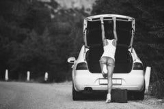 带着手提箱的Womanl在汽车附近 免版税库存照片