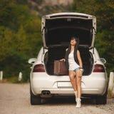 带着手提箱的Womanl在汽车附近 库存图片
