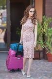 带着把旅馆留在的手提箱的美丽的妇女在一个大城市 与太阳镜的有吸引力的红头发人和在街道上的庄重装束 库存照片
