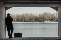 带着抽烟在隧道的手提箱的英俊的成人人在前面 免版税库存图片