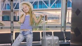 带着旅行手提箱的女孩叫由手机在离开休息室在机场 股票视频