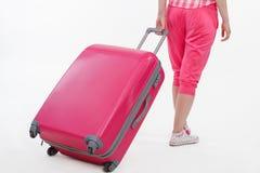 带着桃红色手提箱的女孩旅行家 免版税库存图片