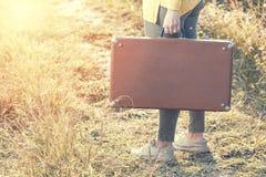 带着棕色葡萄酒手提箱的美丽的少妇在夏天日落期间的领域路 汽车城市概念都伯林映射小的旅行 库存照片