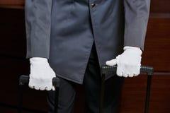 带着白色手套和手提箱的看门人 免版税库存图片