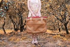 带着皮革手提箱的女孩旅行的在步行的秋天公园 库存图片