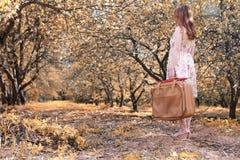 带着皮革手提箱的女孩旅行的在步行的秋天公园 免版税库存照片