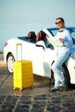 带着看对地图的一个黄色手提箱的少妇在白色附近 免版税库存图片
