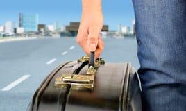 带着离开城市的手提箱的旅行者 免版税图库摄影