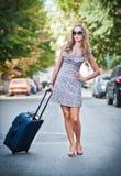 带着穿过街道的手提箱的美丽的妇女在一个大城市 库存照片
