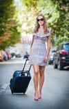 带着穿过街道的手提箱的美丽的妇女在一个大城市 免版税库存图片
