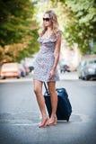 带着穿过街道的手提箱的美丽的妇女在一个大城市 免版税库存照片