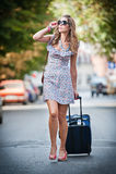 带着穿过街道的手提箱的美丽的妇女在一个大城市 图库摄影