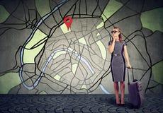 带着站立在一张城市地图的背景的手提箱的少妇与问题的兴趣 库存图片