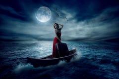 带着站立在一条小船的手提箱的时髦的妇女在海洋的中部 免版税库存图片