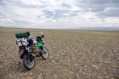 带着站立在多云天气的岩石高原的手提箱的摩托车单独enduro旅客 免版税库存照片
