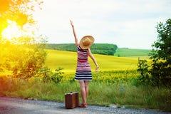 带着站立在太阳的路旁的老手提箱的女孩 免版税图库摄影