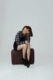带着等待某人的手提箱的一个女孩 免版税图库摄影