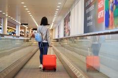 带着红色手提箱的一个女孩在机场 免版税库存照片