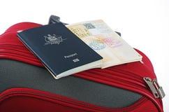 带着红色手提箱的护照 库存图片