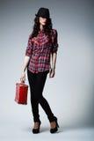 带着红色手提箱的美丽的深色的女孩 库存图片