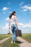 带着老手提箱的俏丽的妇女在远处去 免版税库存图片
