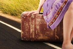 带着老葡萄酒手提箱的妇女在路 免版税库存照片