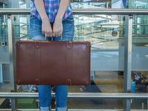带着葡萄酒减速火箭的手提箱的女孩 玻璃篱芭 机场终端 免版税库存照片