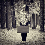 带着葡萄酒手提箱的站立在森林和厕所里的女孩和照相机 库存图片