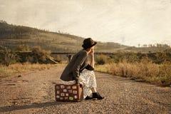 带着葡萄酒旅行手提箱的妇女在路 在老图象s的照片 库存照片