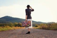 带着葡萄酒旅行手提箱的妇女在路 免版税图库摄影