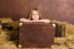 带着葡萄酒褐色手提箱的小逗人喜爱的女孩 库存图片