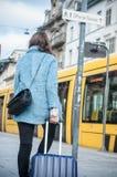 带着蓝色等待电车轨道的外套和手提箱的妇女 免版税库存照片