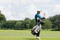 带着他的包的英俊的亚裔高尔夫球运动员人在高尔夫球场与 免版税库存照片