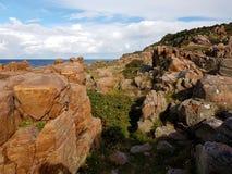 带红色峭壁和岩石在Hovs Hallar,瑞典,由海每晴天 库存图片