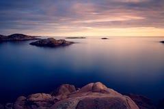 带红色海岛在蓝色海 免版税库存照片
