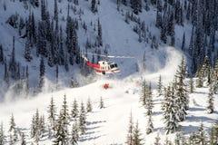 带走滑雪者的直升机 图库摄影