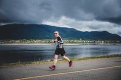 带领一个小组10K赛跑者的孤独的人 免版税库存图片