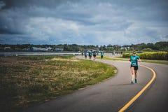 带领一个小组10K赛跑者的孤独的妇女 免版税库存照片