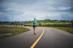 带领一个小组10K赛跑者的孤独的妇女 库存照片