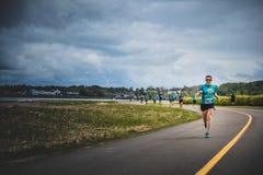带领一个小组10K赛跑者的孤独的妇女 免版税库存图片