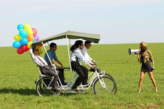 带领一辆方形字体自行车的Baloons妇女4个人在一个绿色领域晴天 免版税库存照片