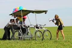 带领一辆方形字体自行车的Baloons妇女4个人在一个绿色领域晴天 免版税库存图片