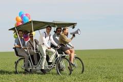 带领一辆方形字体自行车的Baloons妇女4个人在一个绿色领域晴天 库存照片