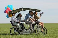 带领一辆方形字体自行车的Baloons妇女4个人在一个绿色领域晴天 库存图片