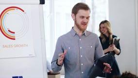 带领交互式办公室训练会议的年轻活跃微笑的白种人商人辅导者,解释flipchart数据 影视素材