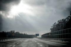 带领入光的平直的沥青路 免版税库存图片