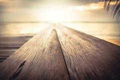 带领入海和天际的热带海滩码头在海在日落期间作为暑假背景 库存照片