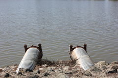 带领入湖的两个排水设备管子 免版税库存照片