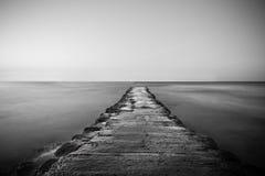 带领在水的防波堤或码头 免版税库存照片
