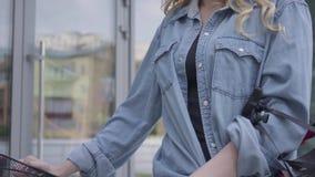 带领她的自行车的白色牛仔裤的年轻亭亭玉立的可爱的白肤金发的妇女在商店窗口附近在城市 热的夫人 股票录像